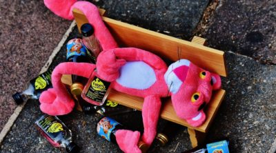 Pink animal passed out with alcohol bottles